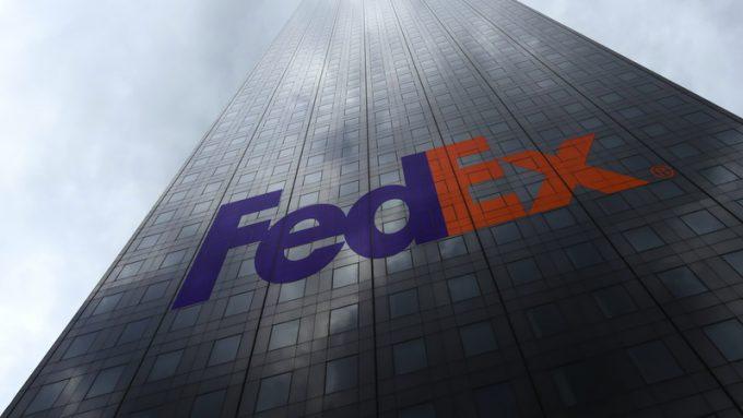FedEx logo on a skyscraper facade reflecting clouds. Editorial 3D rendering