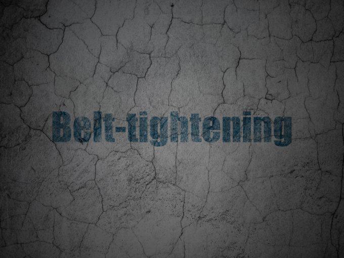 Business concept: Belt-tightening on grunge wall background
