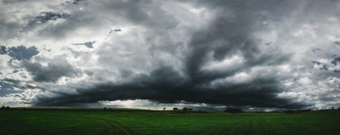 Dark storm clouds panorama above the green grass field