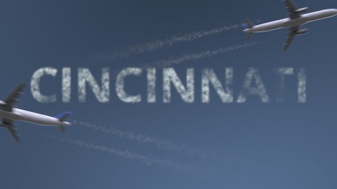 Flying airplanes trails and Cincinnati caption. Traveling to the United States conceptual 3D rendering