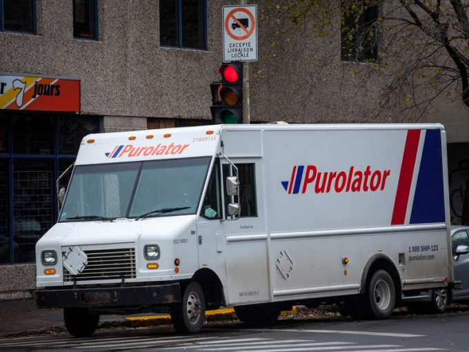 MONTREAL, CANADA - NOVEMBER 6, 2018: Purolator logo on one of their delivery trucks in a street of Montreal, Quebec. Purolator is a Canadian courier specialized in parcels and letters shipping