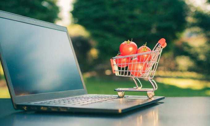 Concept of online grocery shopping. A miniature shopping cart wi