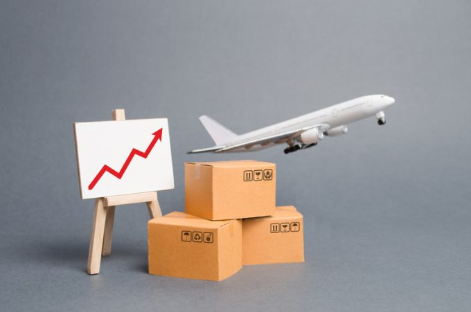 Airplane plane takes off behind stack of cardboard boxes and stand with red up arrow. concept of air cargo and parcels, airmail. Fast delivery of goods and products. Cargo aircraft. Logistics,