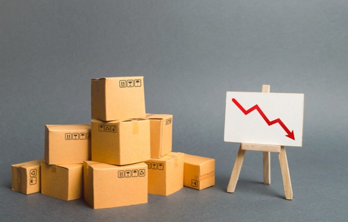 A pile of cardboard boxes and easel with red arrow down. Decrease in the quality, price, quantity and competitiveness of goods and products. Concept drop in industrial production, sales fall.