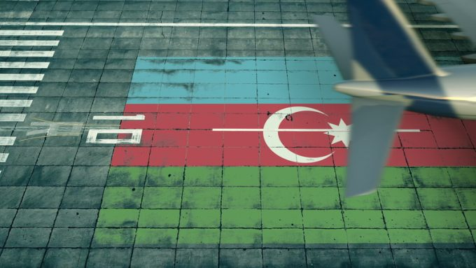 Aerial view of a landing airplane revealing flag of Azerbaijan on the airfield of an airport. Air travel related conceptual 3D rendering