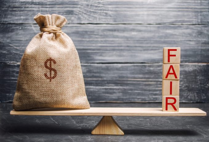 Money bag and wooden blocks with the word Fair. Balance. Fair value pricing, money debt. Fair deal. Reasonable price. Justified risk. Honest loan. Secured loans.