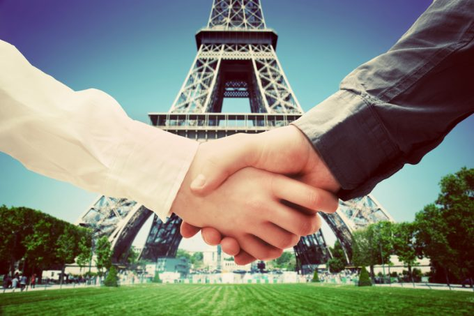 Business in Paris, France. Handshake on Eiffel Tower background