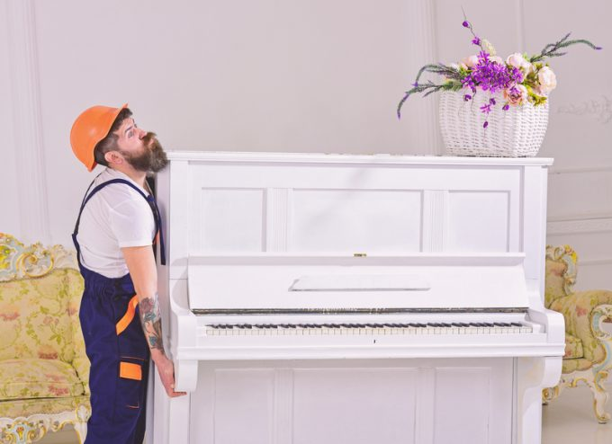 Loader moves piano instrument. Courier delivers furniture in case of move out, relocation. Delivery service concept. Man with beard, worker in overalls and helmet lifts up piano, white background