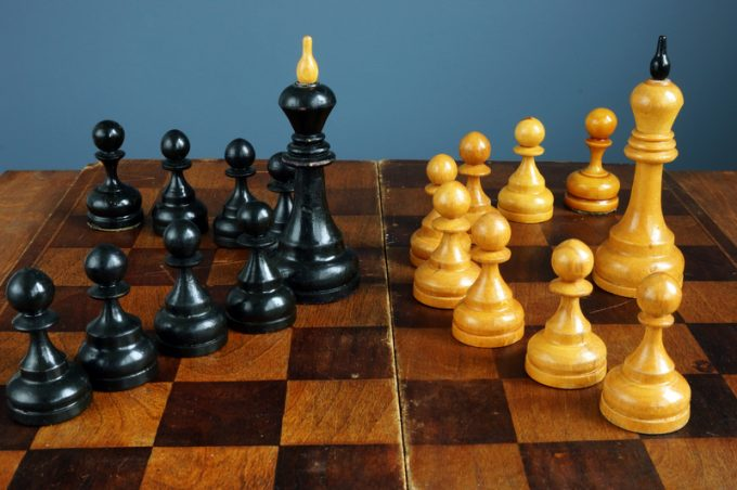 Leader vs boss or manager. Chess kings and pawns on desk.