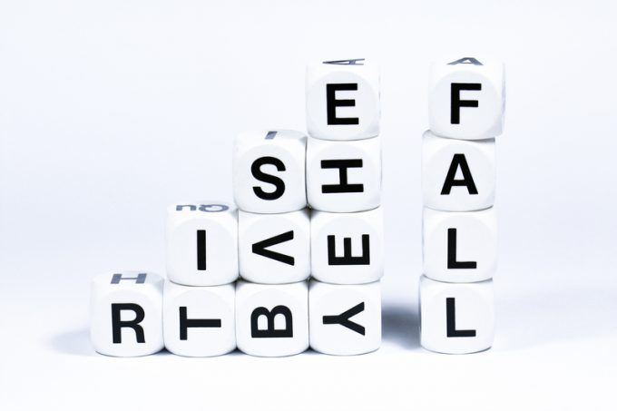 Lettered dice spelling out the words rise and fall on a white background