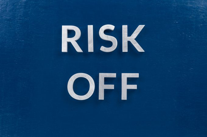 the words risk off laid with silver metal letters on classic blue surface for stock market background